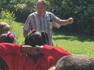 Man teaching children outdoors