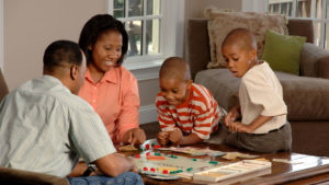 A mom and dad with their two young boys are playing a board game on the table in the living room